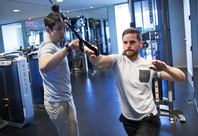 Dalton Wong guiding reporter Jonathan Forani through a combat pull cable machine